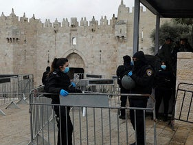 Israeli security forces, wearing protective face masks, stand guard in front of the Damascus Gate in Jerusalem's Old City on March 20, 2020.