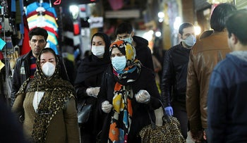 People wear protective face masks and gloves as they walk at Tajrish market, ahead of the Iranian New Year Nowruz in Tehran, March 18, 2020.