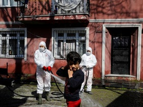 Workers in protective suits disinfect a street as a girl stands in front of them in Istanbul, Turkey, March 20, 2020.