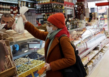 A woman with a face mask buys goods in a delicatessen, in Ankara, Turkey, March 18, 2020.