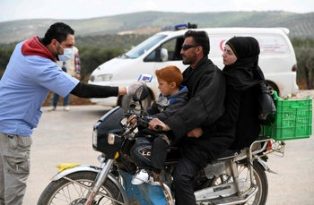 A temperature check near a camp for displaced Syrians near the border with Turkey, March 17, 2020.