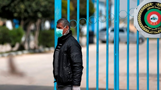 A Palestinian health ministry officer stands at the gate of the Erez crossing with Israel near Beit Hanun in the northern Gaza Strip on March 15, 2020.