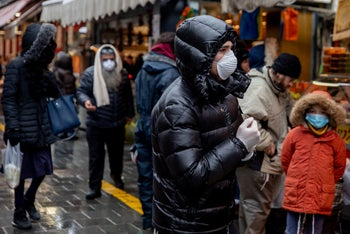 People wearing protective masks while walking in Jerusalem's Mahane Yehuda market, March 20, 2020.