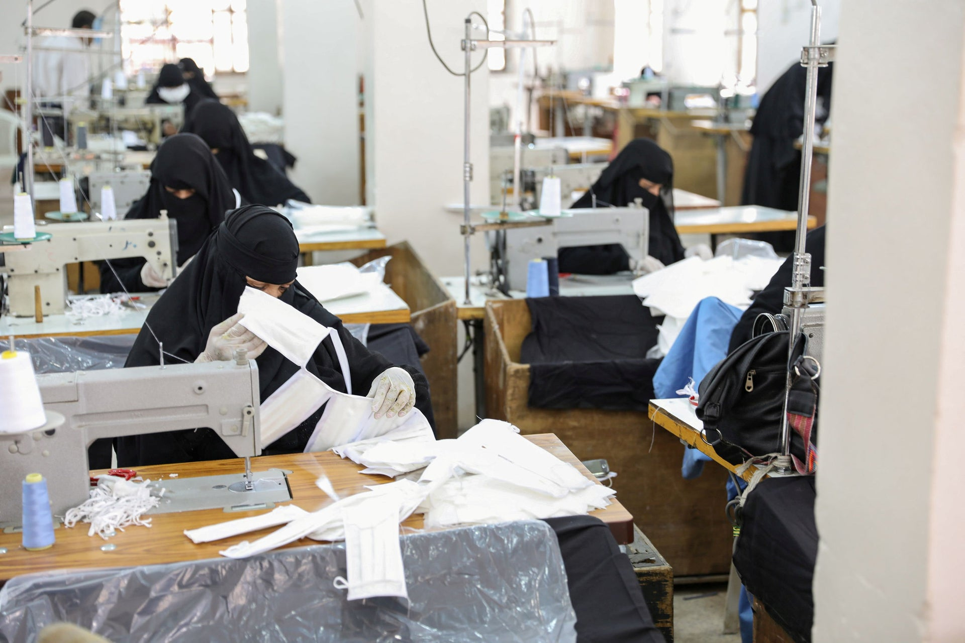 Yemeni women work to manufacture protective face masks at a textile factory in Sanaa, Yemen, March 17, 2020.