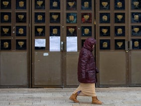 A woman walks past the Great Synagogue in Jerusalem, shuttered over the coronavirus outbreak, March 30, 2020.