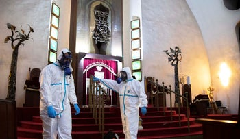 Workers sprays disinfectant as a precaution against the coronavirus at the Great Synagogue in Tel Aviv, Israel, March 17, 2020.