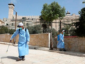 Palestinians from the rehabilitation committee of Hebron disinfect the Ibrahimi Mosque, or the Tomb of the Patriarchs, in the West Bank city of Hebron on March 11, 2020.