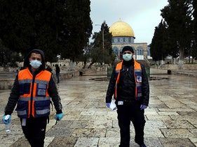 Palestinian volunteers in front of the Dome of the Rock at the Temple Mount, in Jerusalem's Old City, March 20, 2020.