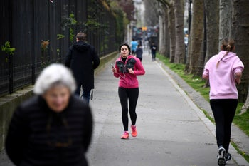 Joggers run along the Monceau Park in Paris, on March 22, 2020, on the sixth day of a strict lockdown in France aimed at curbing the spread of COVID-19.
