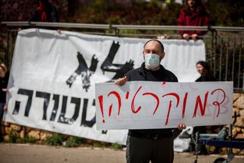 """Protestor holds a sign reading in Hebrew: """"Democracy"""" in front of a sign reading """"No to dictatorship"""" outside the Knesset in Jerusalem. March 19, 2020"""