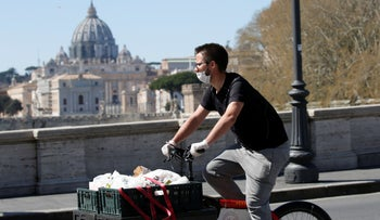A delivery person passes near St. Peter's Basilica, as Italy tightens measures to try and contain the spread of coronavirus, Rome, Italy, March 23, 2020.