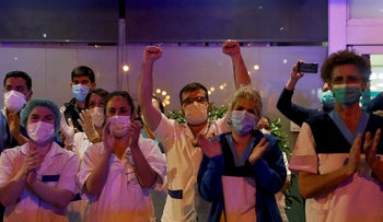 Medical staff from the Fundacion Jimenez Diaz hospital applaud as neighbours applaud from their balconies in support for healthcare workers, during the coronavirus disease (COVID-19) outbreak, in Madrid, Spain March 23, 2020