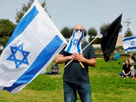 An Israeli man wearing a mask against coronavirus holds his national flag and a black flag during a protest outside the Knesset in Jerusalem on March 23, 2020.