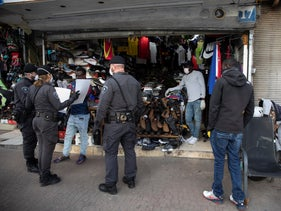 Police hand out fliers about the coronavirus to migrant workers and asylum seekers in Tel Aviv's Neveh Sha'anan neighborhood, March 22, 2020.