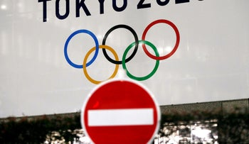 A banner for the Tokyo 2020 Olympics is seen behind a traffic sign in Tokyo, Japan, March 23, 2020.