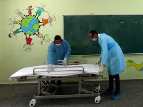 Palestinian health workers prepare a stretcher at a United Nations Relief and Works Agency for Palestinian Refugees school at al-Shati refugee camp in Gaza City, March 18, 2020.