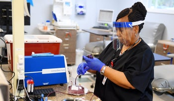 A medical worker prepares two packs of packed red blood cells for shipment, Vero Beach, Florida, March 19, 2020.