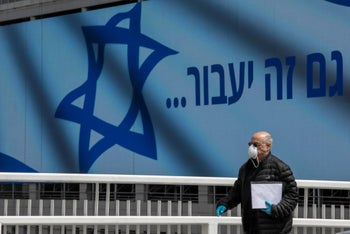 A man wearing a protective mask standing next to the Israeli flag with the writing 'This too shall pass,' March 2020.