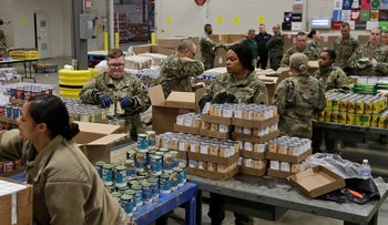 In this March 24, 2020, file photo, members of The Ohio National Guard assist in repackaging emergency food boxes for food distribution at the Cleveland Food Bank in Cleveland