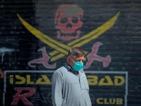 A Pakistani man wearing a facemask walks past closed market shops in Karachi on March 22, 2020, after the Punjab provincial government closed markets amid concerns over the spread of the COVID-19 coronavirus