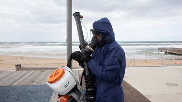 A worker disinfects a park on a Bat Yam beach, March 18, 2020.