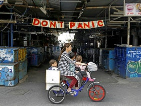 A woman rides a bicycle with her children past a banner hanging at the entrance of Shuk HaCarmel (Caramel) market in the Israeli coastal city of Tel Aviv on March 24, 2020.