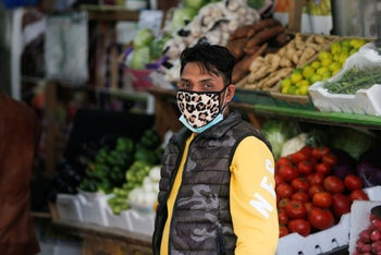 A vendor wears a protective face mask following the coronavirus outbreak, at a local vegetables and fruits market in Sanabis west of Manama, Bahrain February 27, 2020.