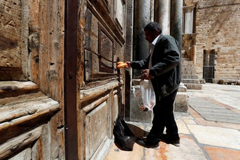 A man passes food through a hole in the closed front door of the Church of the Holy Sepulchre amid coronavirus restrictions in Jerusalem's Old City  March 26, 2020
