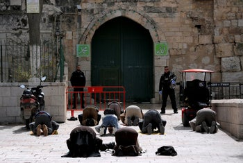 Muslim worshippers pray near a closed gate of the compound housing Al-Aqsa mosque in Jerusalem's Old City, March 23, 2020.