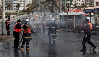Members of the Palestinian civil defense force spray disinfectant in the port area in Gaza City on March 24, 2020.