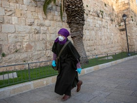 A woman wearing a masks walks outside the walls of the Old City of Jerusalem, March 24, 2020.