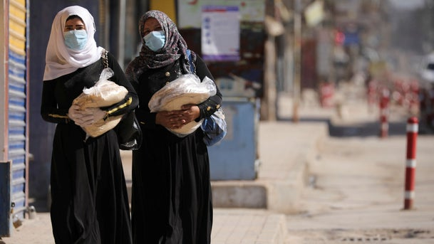 Women hold stacks of bread as they walk along an empty street, as restrictions are imposed as measure to prevent the spread of the coronavirus in Qamishli, Syria, March 23, 2020.