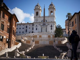 A man rides his scooter past the empty Spanish Steps, in Rome, amid the coronavirus outbreak.