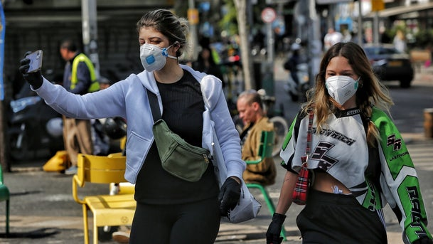 Pedestrians with face masks in Tel Aviv, March 2020.