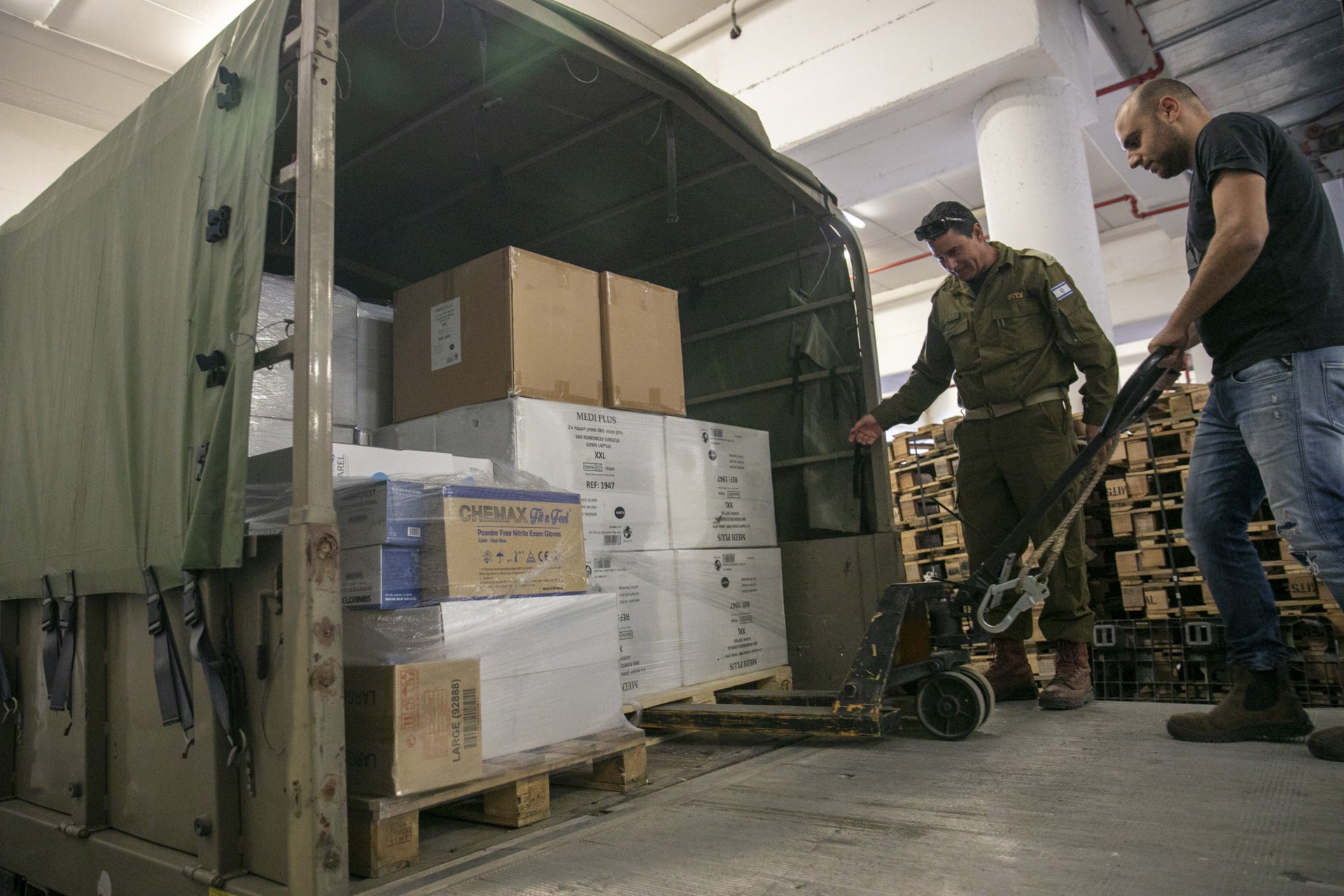 An Israeli soldier and a Sarel employee loading a truck in the Sarel warehouse, Netanya, March 17, 2020.
