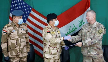 U.S. Brigadier General Vincent Barker shakes hands with Iraqi General Mohammed Fadel during the hand over of Qayyarah Airfield West from US-led coalition forces to Iraqi Security Forces, March 26, 2020.
