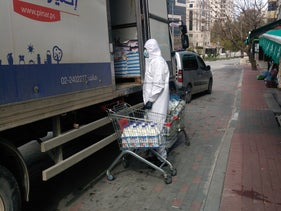 Palestinian men unload yogurt from a truck in Ramallah - all the shelves in the supermarket were fully stocked.