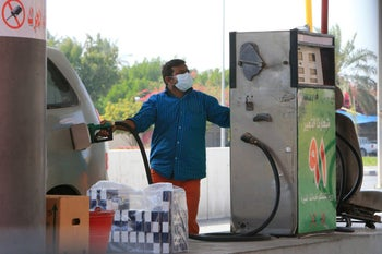 A foreign worker wearing a protective mask fills a car tank at a petrol station in Qatif city in the Eastern Province, some 400Km from the capital Riyadh, Saudi Arabia, March 9, 2020.