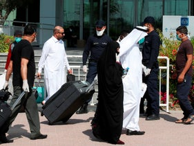 Qatari police stand outside a hotel in Doha as a medical worker walks alongside people wearing protective masks over fears of coronavirus, March 12, 2020.