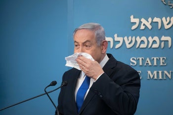 Netanyahu demonstrates blowing his nose at a press conference in the Prime Minister's Office, March 11, 2020.