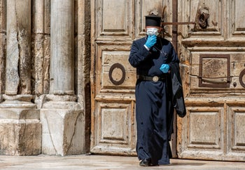 A monk at the Church of the Holy Sepulcher in Jerusalem's Old City dons a face mask, March 26, 2020.