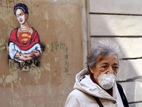 A woman wearing a face mask walks through the Jewish district in central Rome, Italy, March 24, 2020.