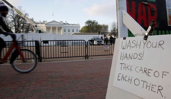 """A sign reminding people to """"wash your hands"""" during the current coronavirus outbreak hangs on the semi-permanent anti-nuclear weapons White House Peace Vigil across from White House in Washington, U.S. March 26, 2020"""