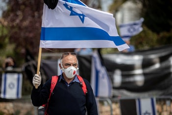 A man wearing a protective mask and waving the Israeli flag while demonstrating in from of the Knesset in Jerusalem, March 25, 2020.