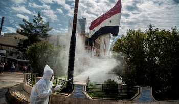 Workers disinfect the streets to prevent the spread of coronavirus in Qamishli, Syria, Tuesday, March 24, 2020.