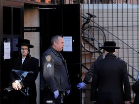 New York City police officers block Hasidic Jewish men from entering a synagogue, closed due to the coronavirus, in Brooklyn, New York, March 18, 2020.