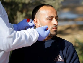 A Palestinian worker is swabbed by a medical worker for coronavirus upon his return from Israel, at Tarqumiya checkpoint near Hebron, West Bank, March 24, 2020.