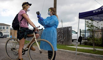 Elena Likaj, prevention department manager at Odyssey House Louisiana (OHL) which runs a drive-through testing site, takes the temperature of New Orleans resident Peyton Gill as OHL began testing bikers for the coronavirus disease (COVID-19) in New Orleans, Louisiana, U.S. March 27, 2020