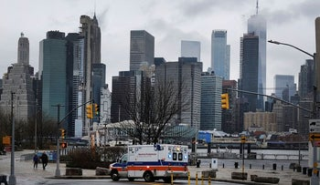 An ambulance pauses in Brooklyn while lower Manhattan looms in the background on March 28, 2020 in New York City, NY