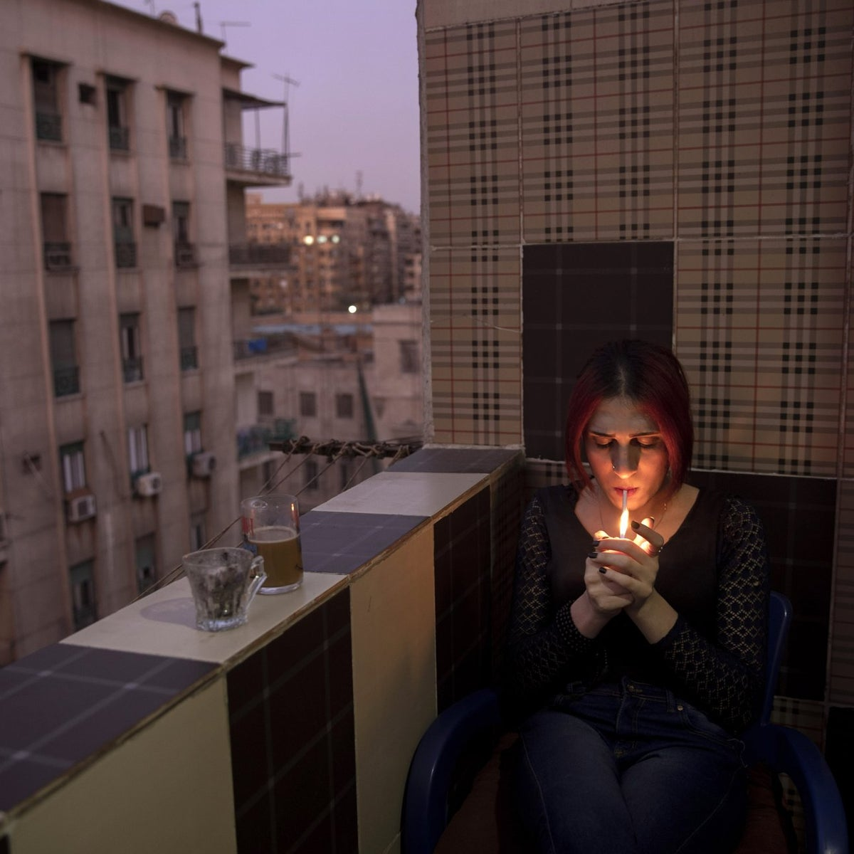 Malak el-Kashif smokes a cigarette in the balcony of her apartment in Cairo, Egypt.